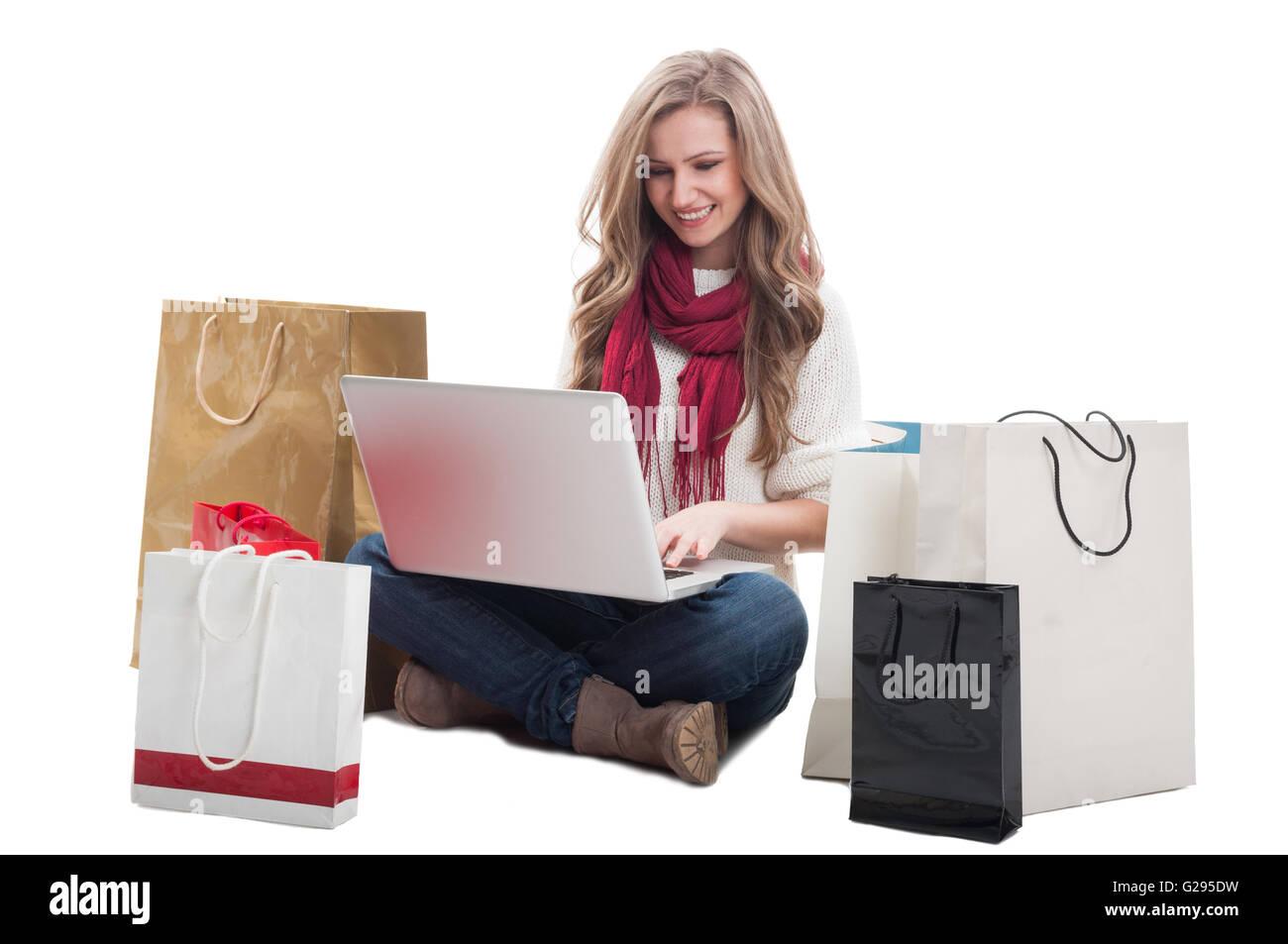 28701f632c83d L'achat en ligne en utilisant l'ordinateur portable femme et assis sur le sol  avec des sacs de shopping