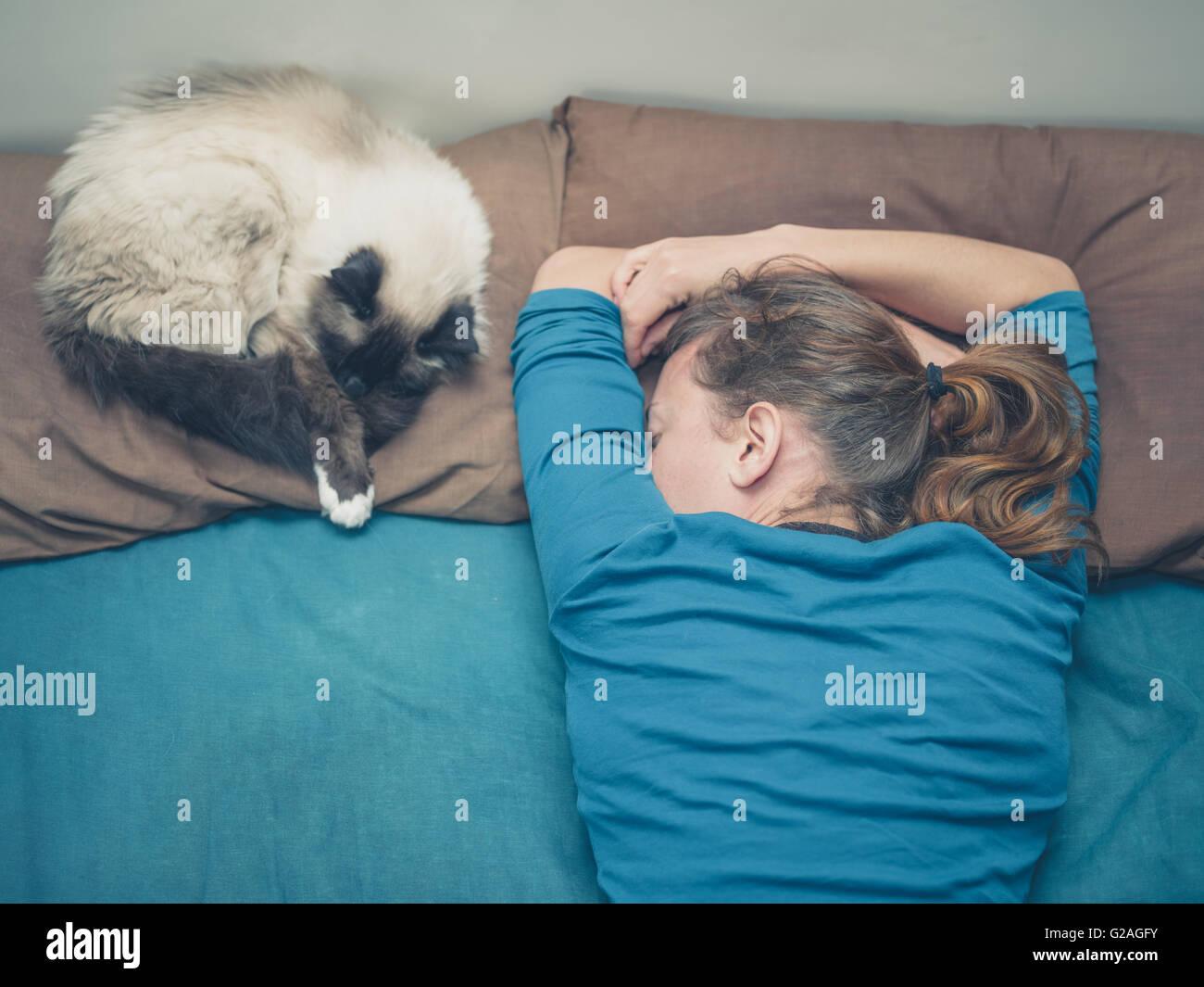 Une jeune femme est en train de dormir dans un lit avec un chat à côté d'elle Photo Stock