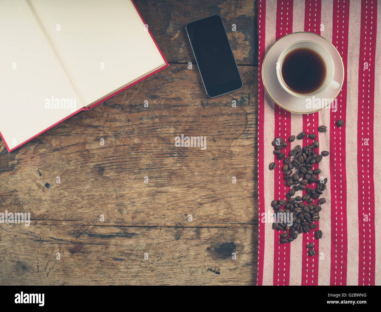 Coup de frais généraux de café concept avec tasse de thé, une serviette, un livre ouvert et un téléphone intelligent Banque D'Images