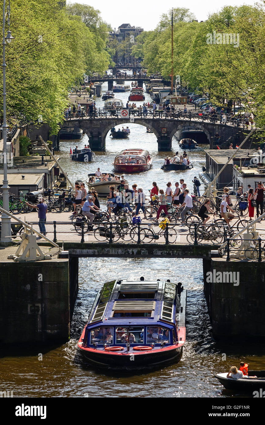 Canaux d'Amsterdam. Quatre ponts avec beaucoup de cyclistes sur le canal Prinsengracht avec canal bateaux d'excursion Photo Stock