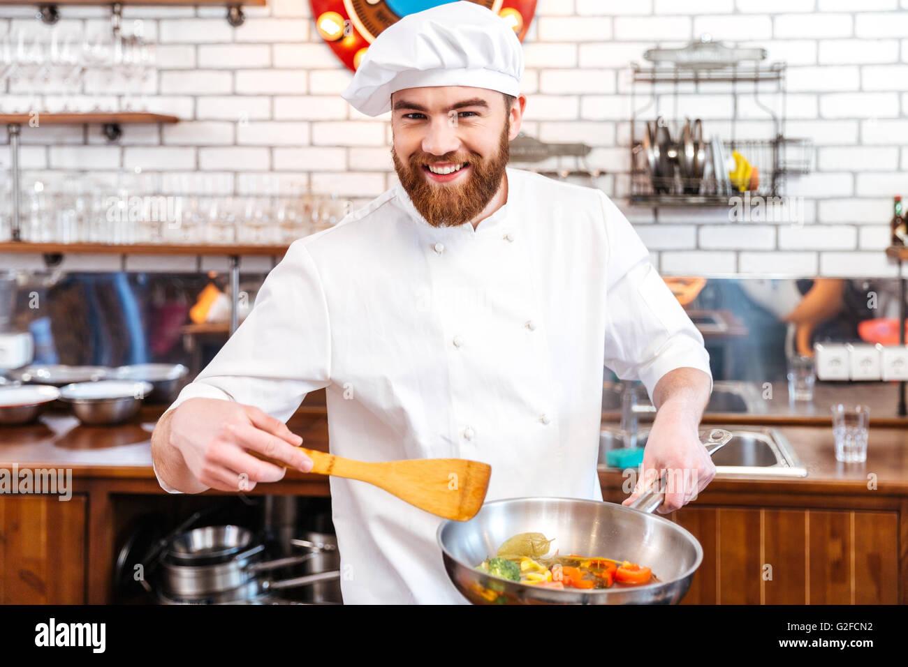 Happy chef cuisine attrayante à l'aide de cuisson poêle sur la cuisine Photo Stock