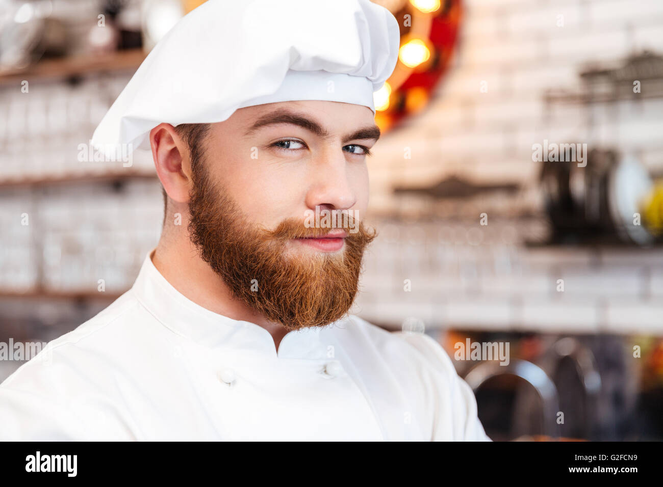 Libre de handsome smiling chef cuisinier barbu dans white hat et uniforme sur la cuisine Photo Stock