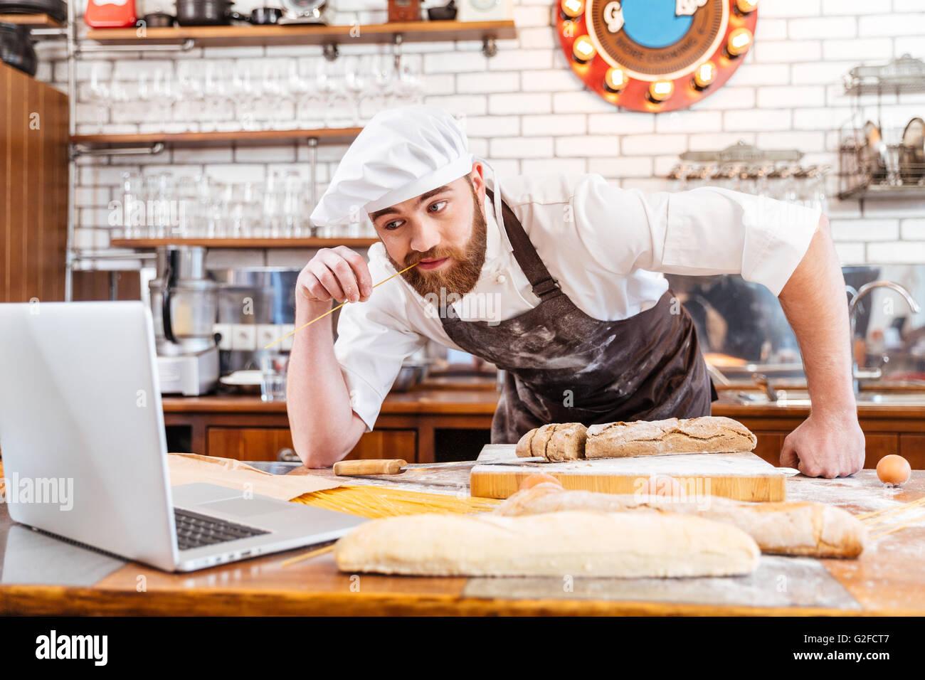 Barbu réfléchies et pain coupe Baker à l'aide d'un ordinateur portable sur la cuisine Photo Stock