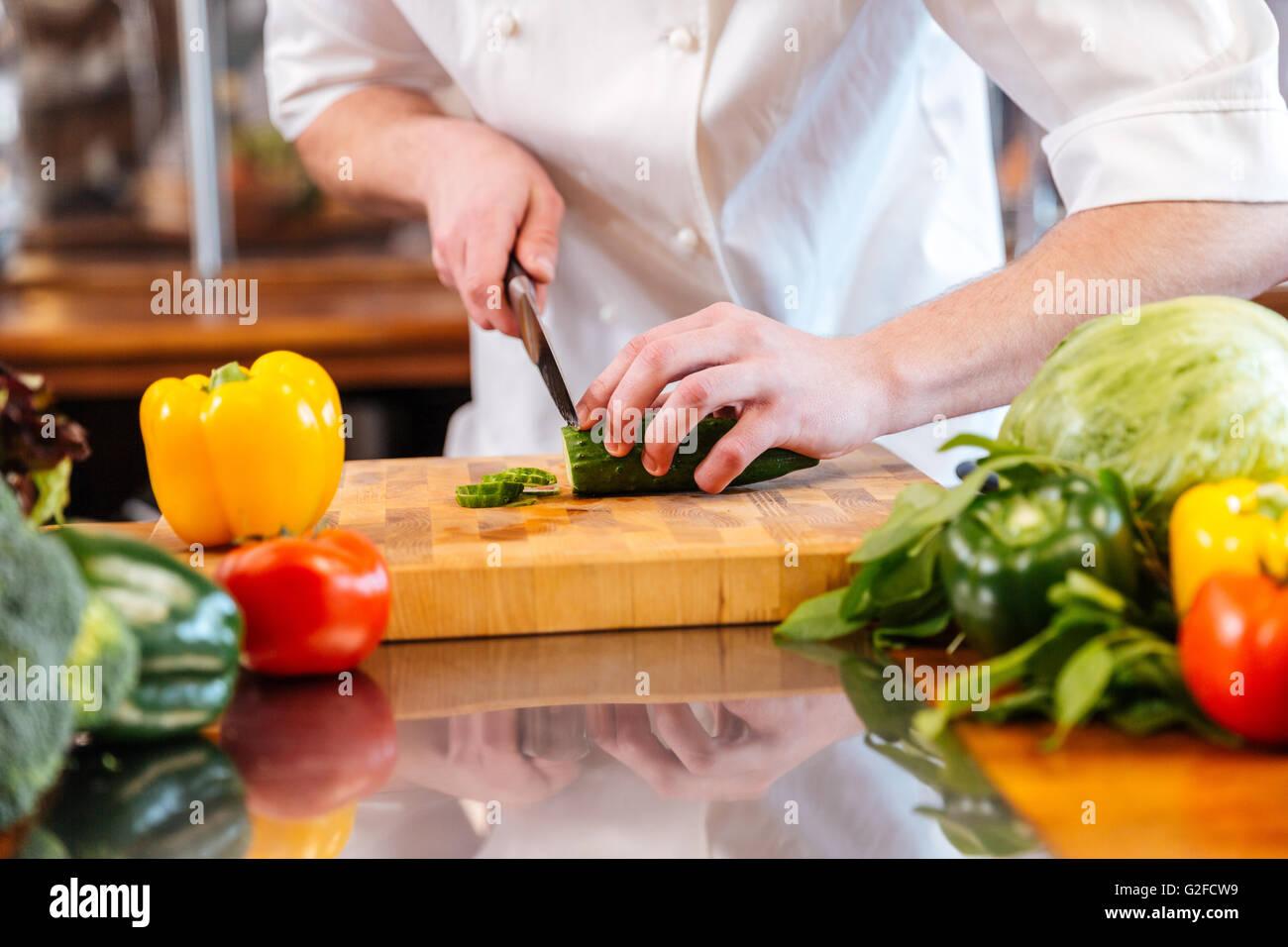 Gros plan du concombre vert réduit de mains de chef cuisinier professionnel sur la cuisine Photo Stock
