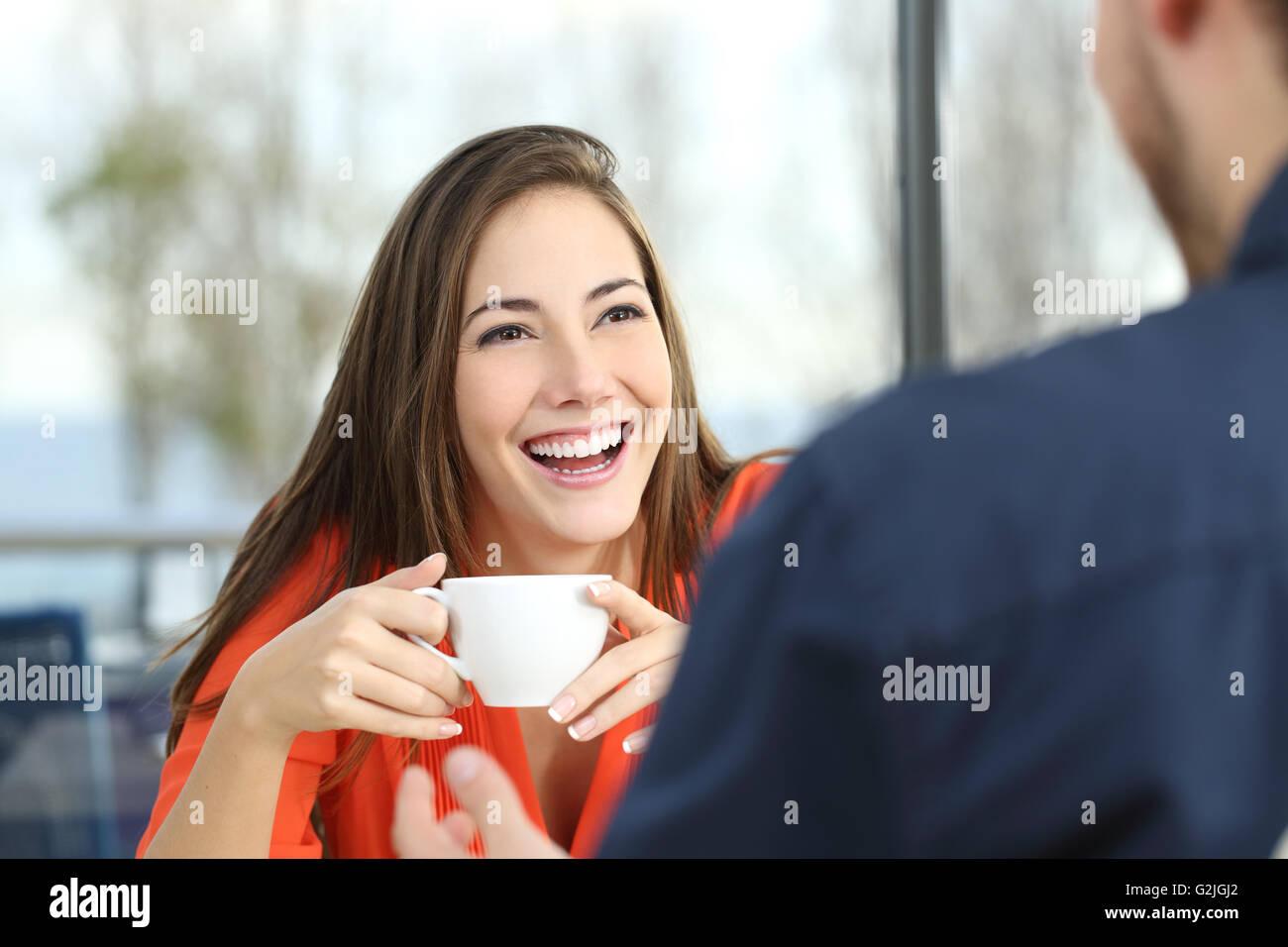 Happy woman dating dans un café en regardant son partenaire et tenant une tasse Photo Stock