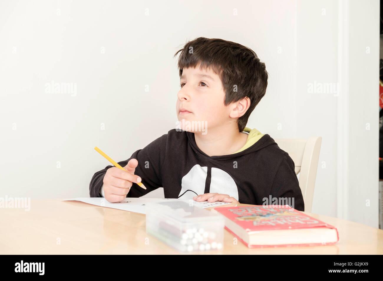 Travailler sur ses devoirs d'écolier Photo Stock