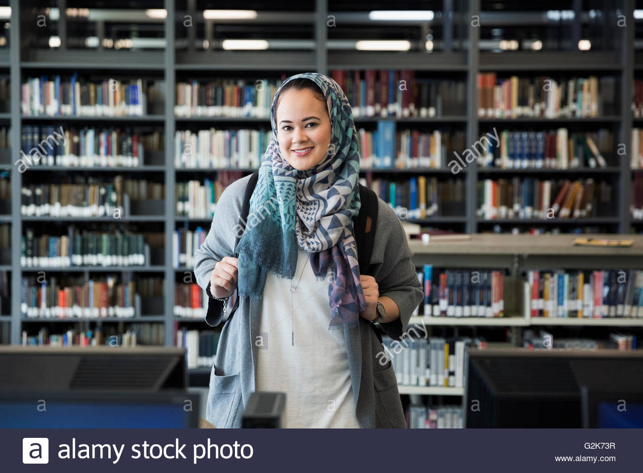 Portrait of smiling college student wearing hijab in library Photo Stock