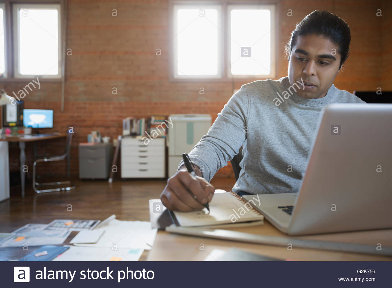 La prise de notes Designer at laptop in office Photo Stock