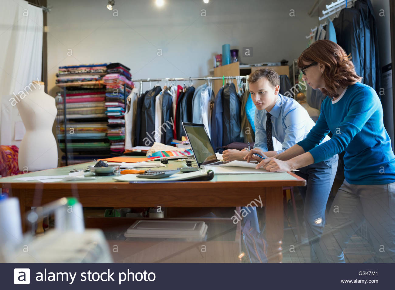 Couturiers working at laptop à workbench Photo Stock