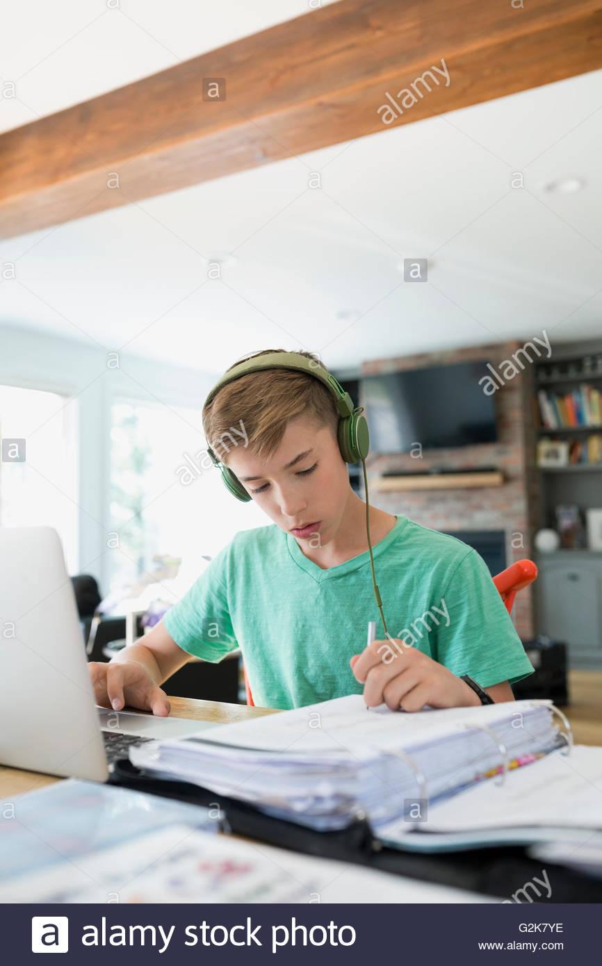 Garçon avec un casque à l'aide ciblée à leurs devoirs d'ordinateur portable Photo Stock