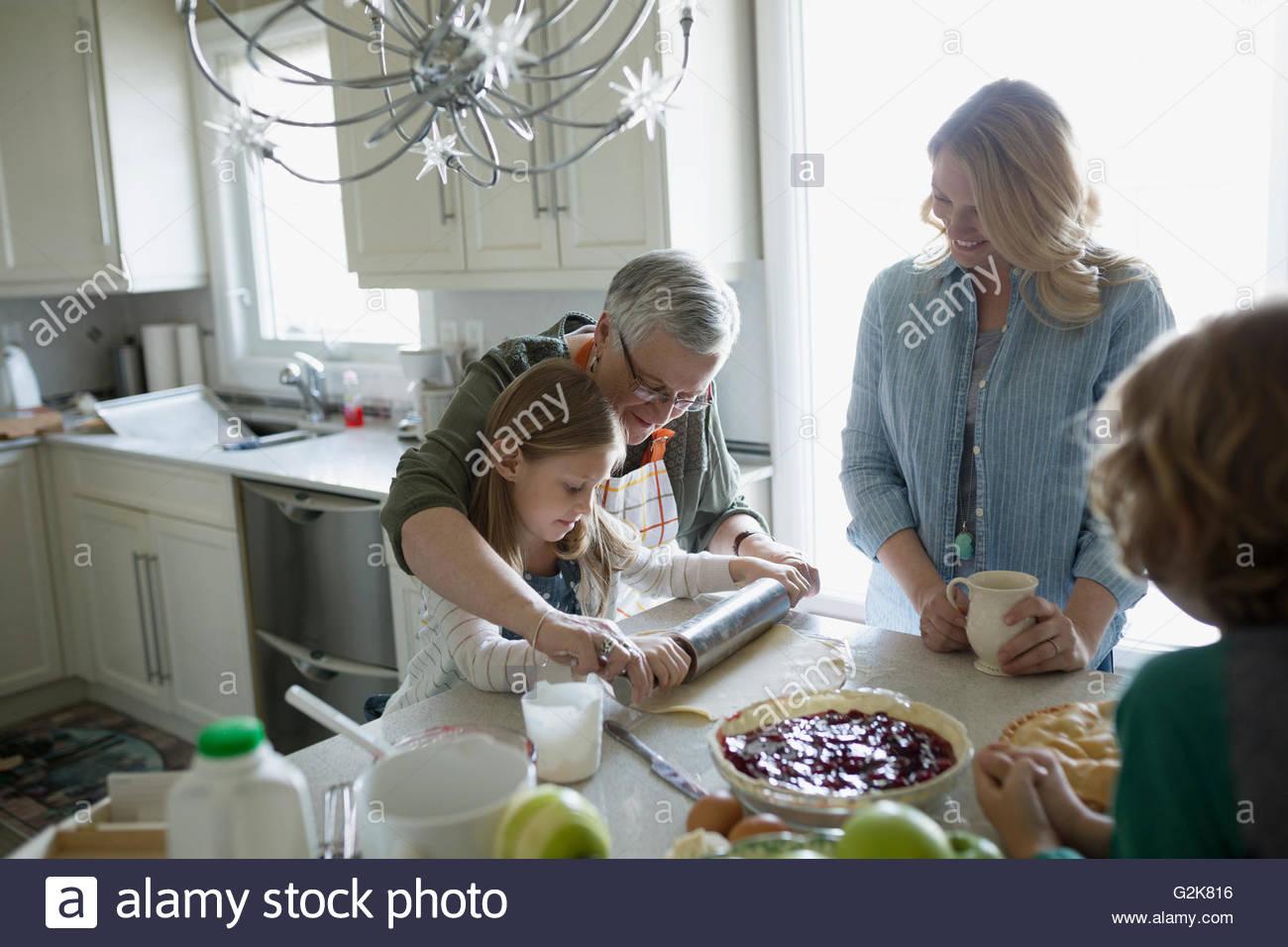 Multi-generation family baking cherry pie dans la cuisine Photo Stock