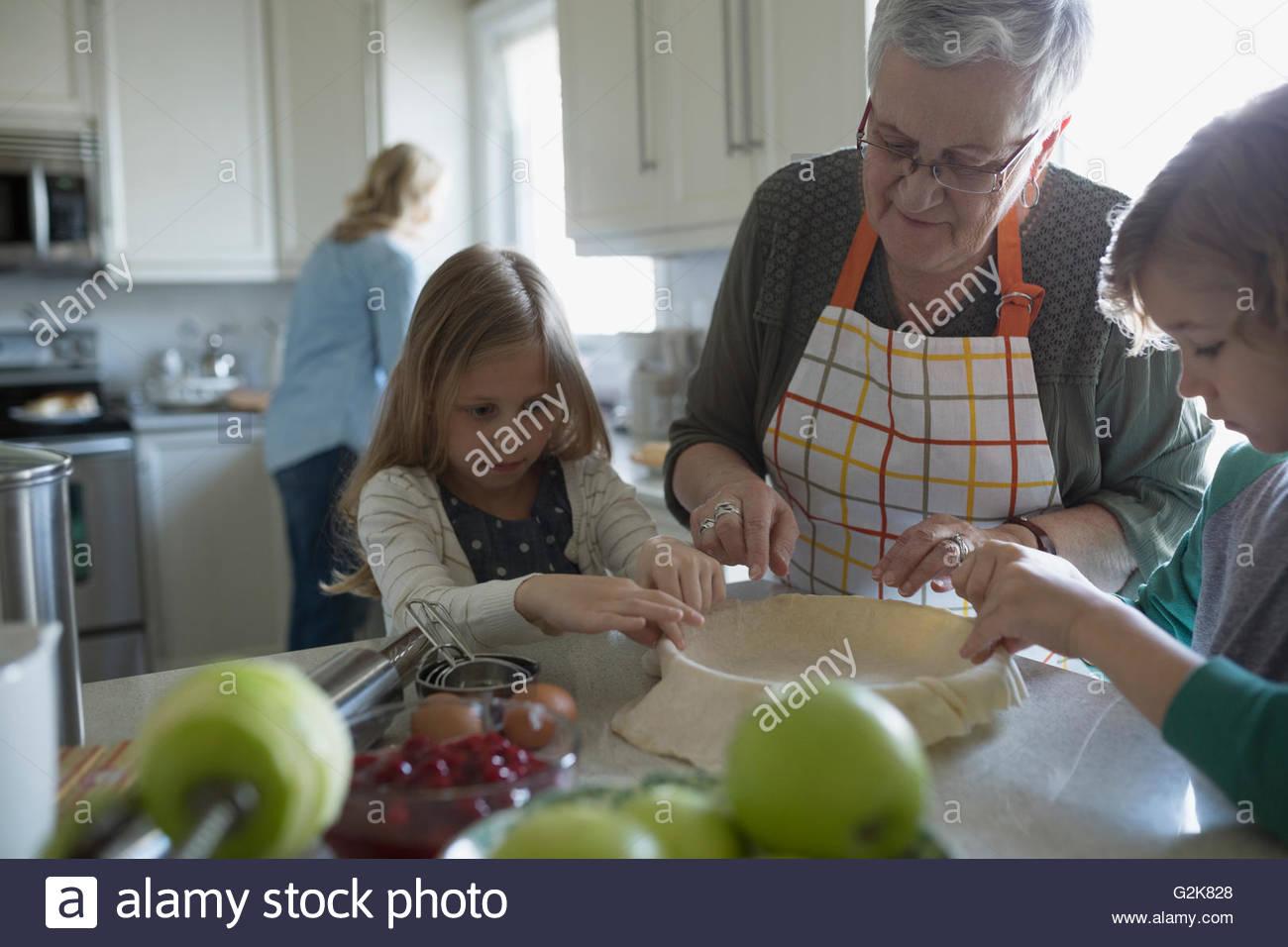 Grand-mère et ses petits-enfants apple pie de cuisson dans la cuisine Photo Stock
