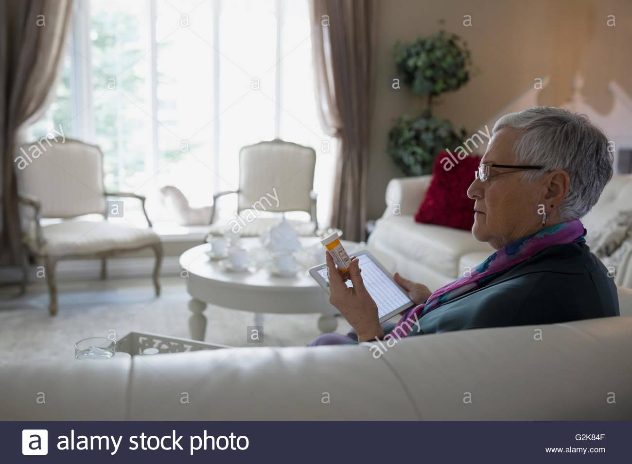 Senior woman with digital tablet contrôle étiquette de prescription Photo Stock