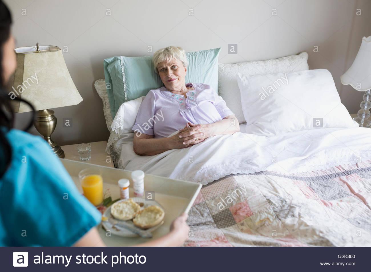 Aide familiale servant le petit-déjeuner et des médicaments pour senior woman in bed Photo Stock