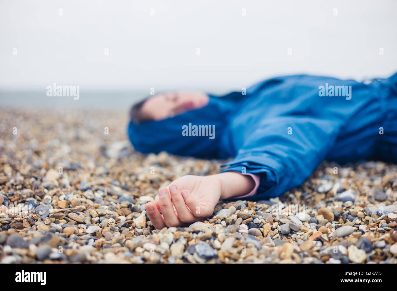 Une femme inconsciente est allongé sur une plage de galets Photo Stock