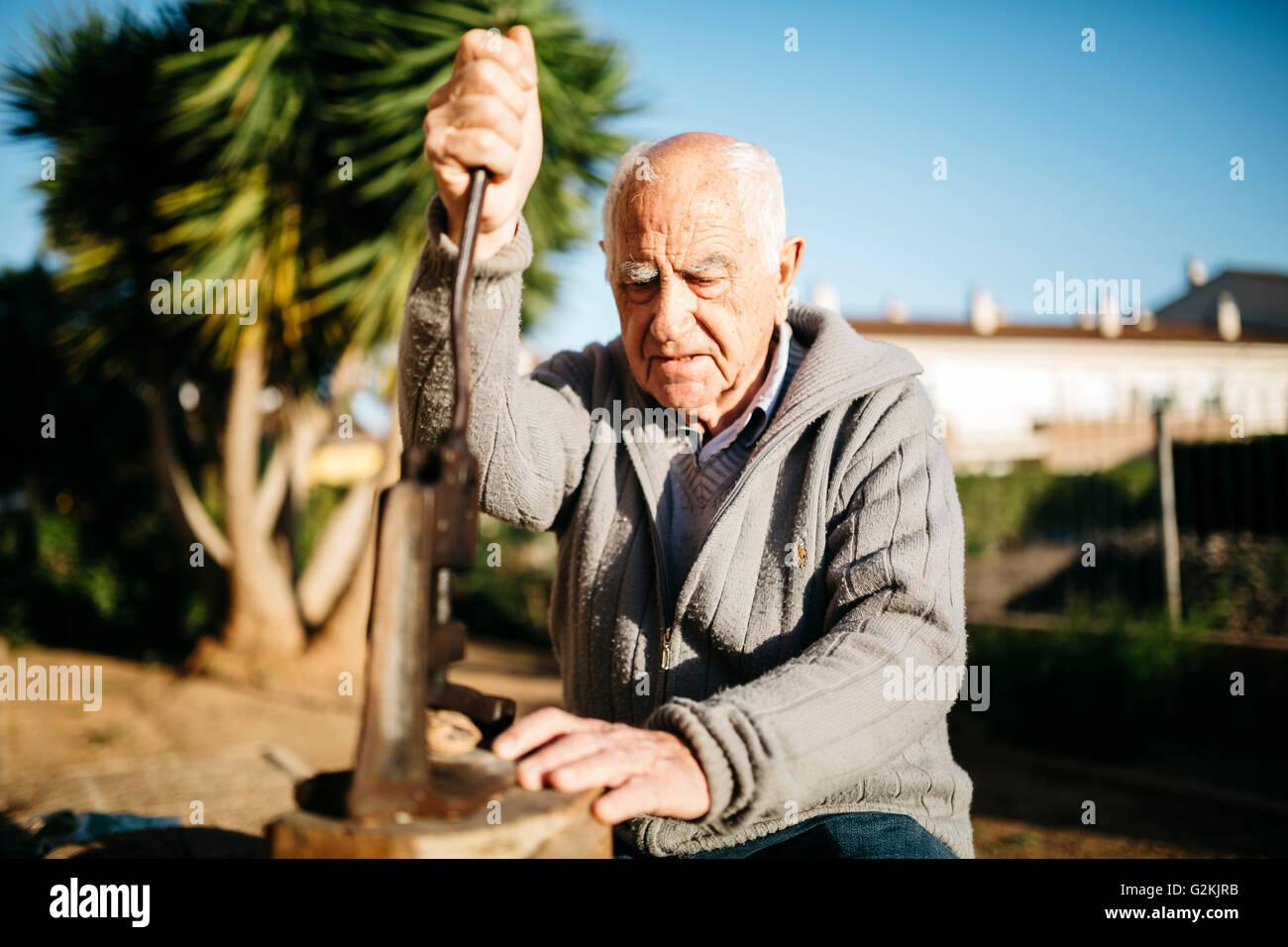 Man à l'aide d'un outil ancien pour fissurer les noix Photo Stock