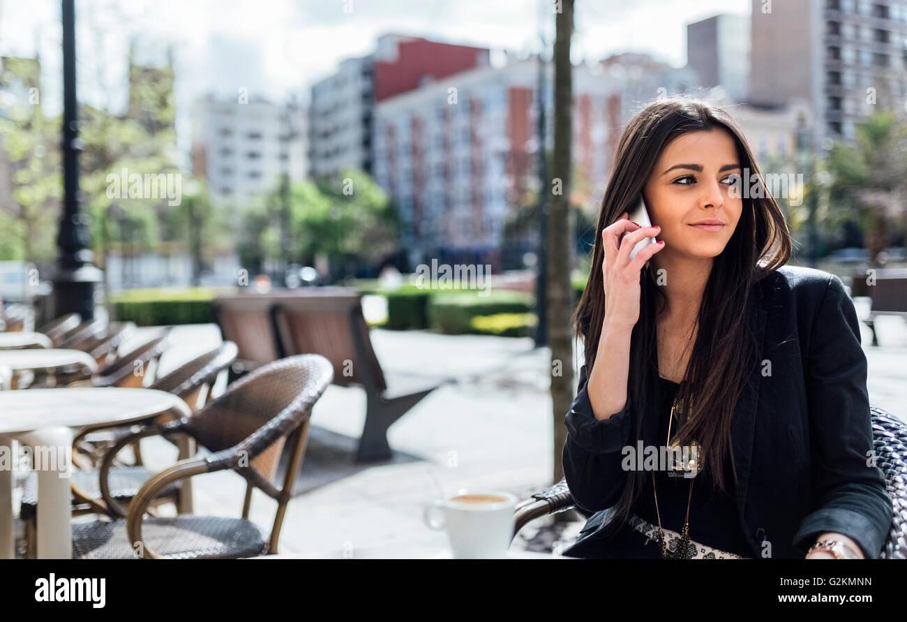 Jeune femme avec le smartphone le café Banque D'Images