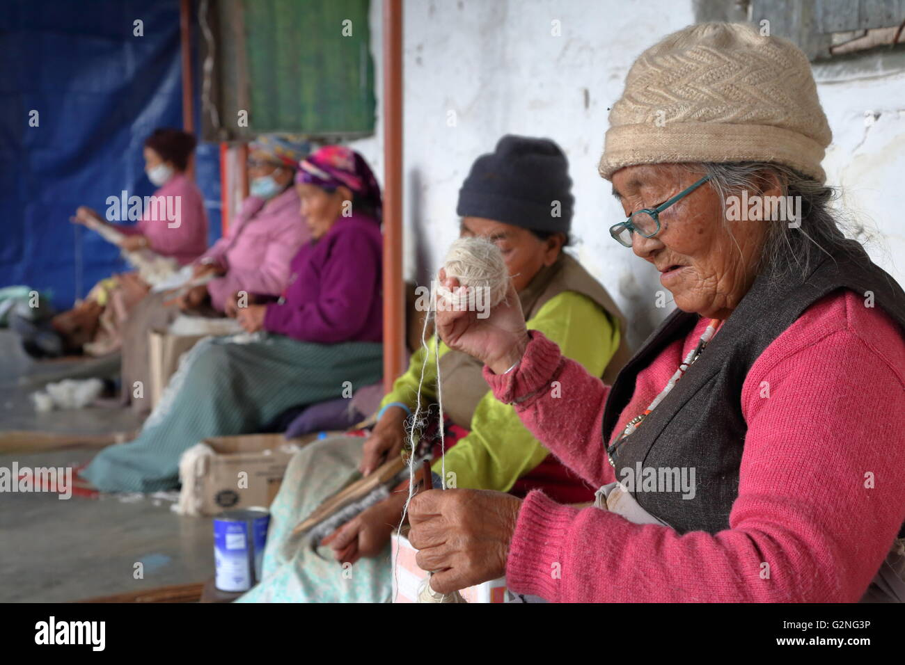 Les femmes tibétaines filage de la laine au camp de réfugiés tibétain Tashi Palkhel, Pokhara, Photo Stock
