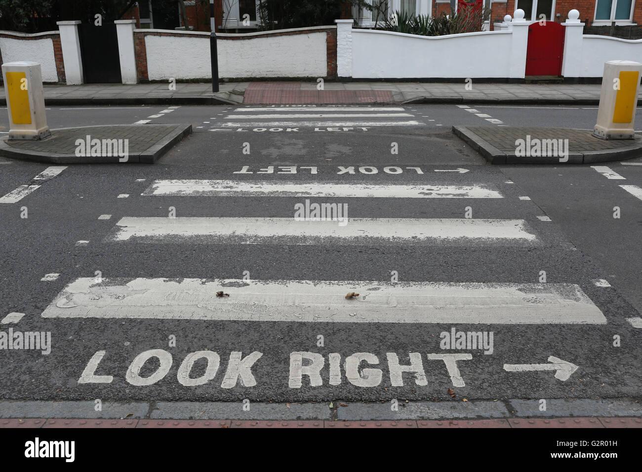 Passage pour piétons avec regardez à droite, à gauche le marquage routier, bollards, signes contre Photo Stock