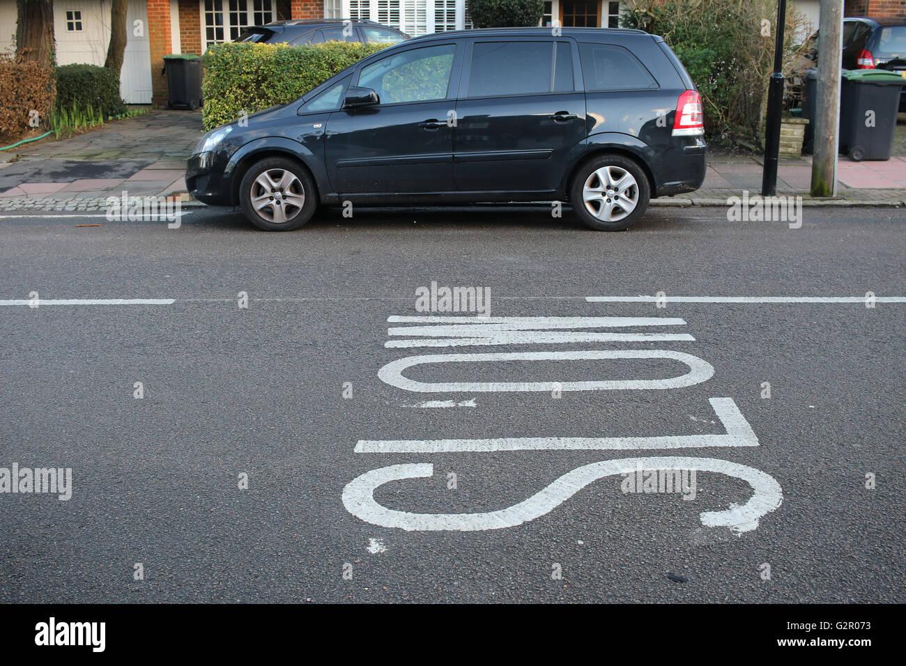 Le marquage routier lent contre un minibus Vauxhall Zafira, maisons Photo Stock
