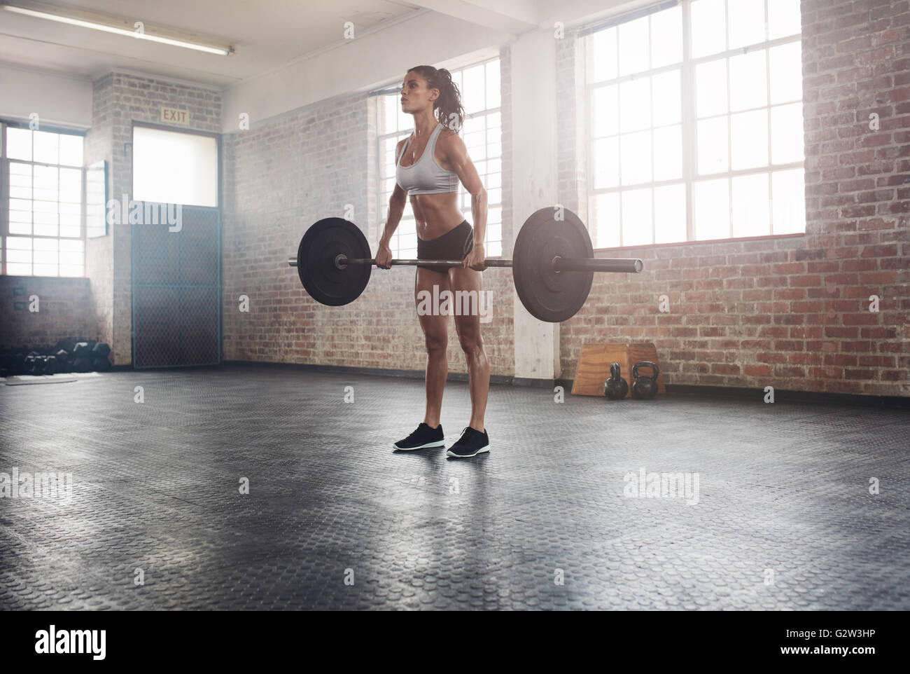 Femme de remise en forme à la préparation pratique soulevé de terre avec des poids lourds en salle Photo Stock