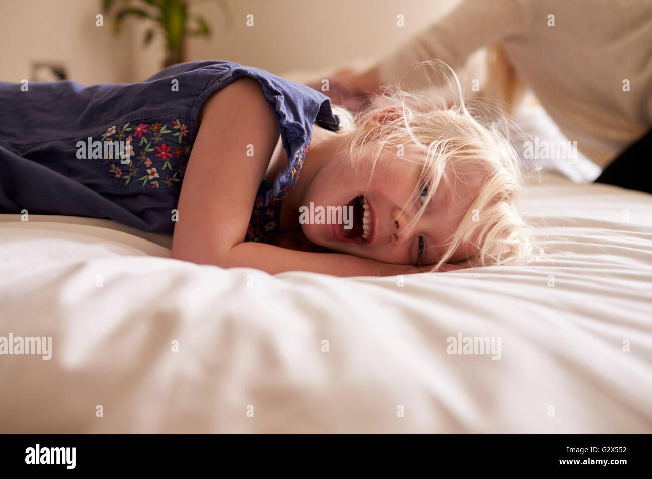 Portrait de jeune fille couchée sur le lit des parents Banque D'Images