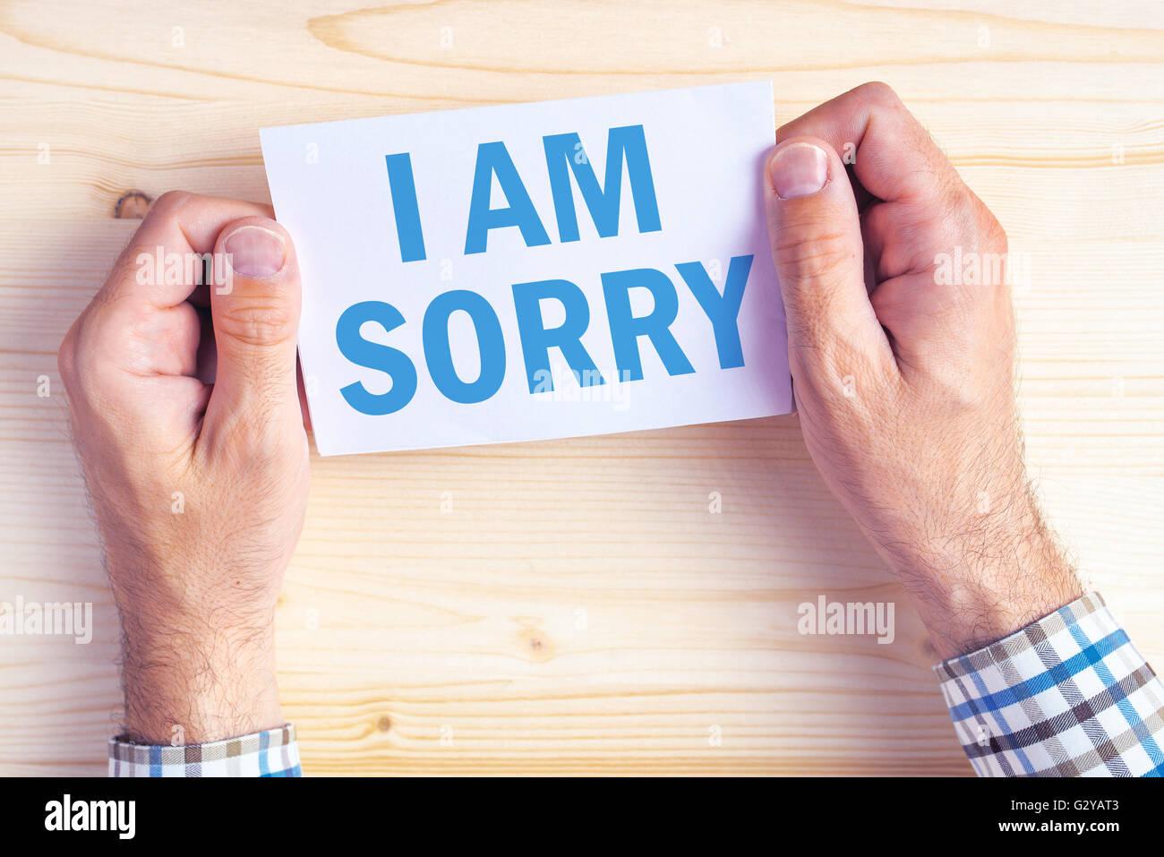 Je suis désolé message, vue de dessus de male hands holding carte excuses Photo Stock