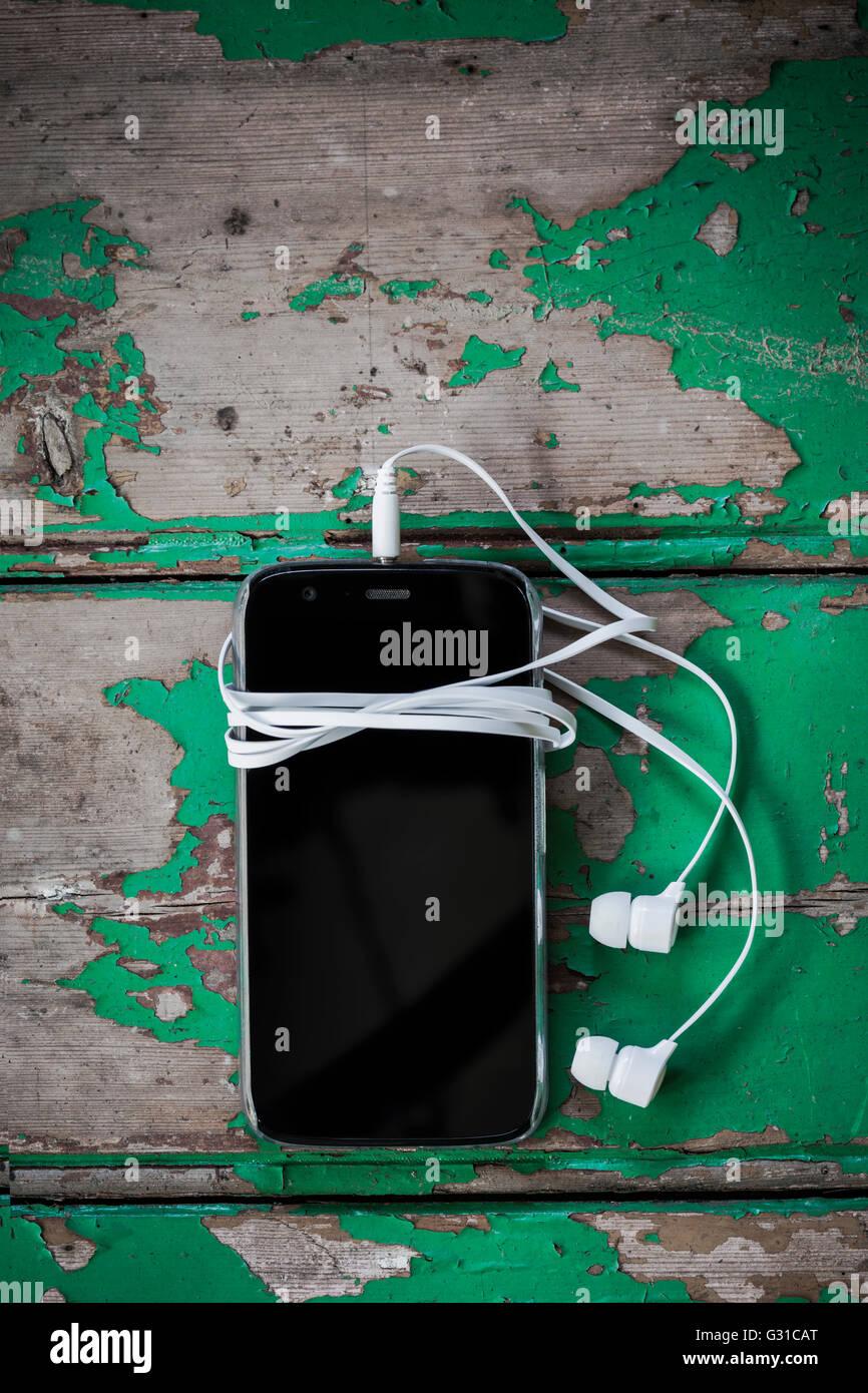 Téléphone mobile avec un casque. Photo Stock