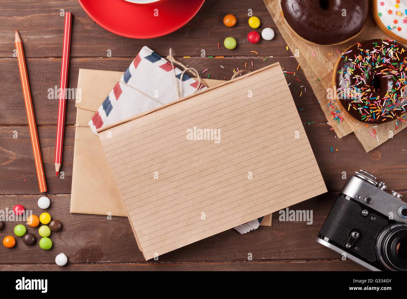 Le bloc-notes, des beignes et du café sur la table en bois. Top View with copy space Banque D'Images
