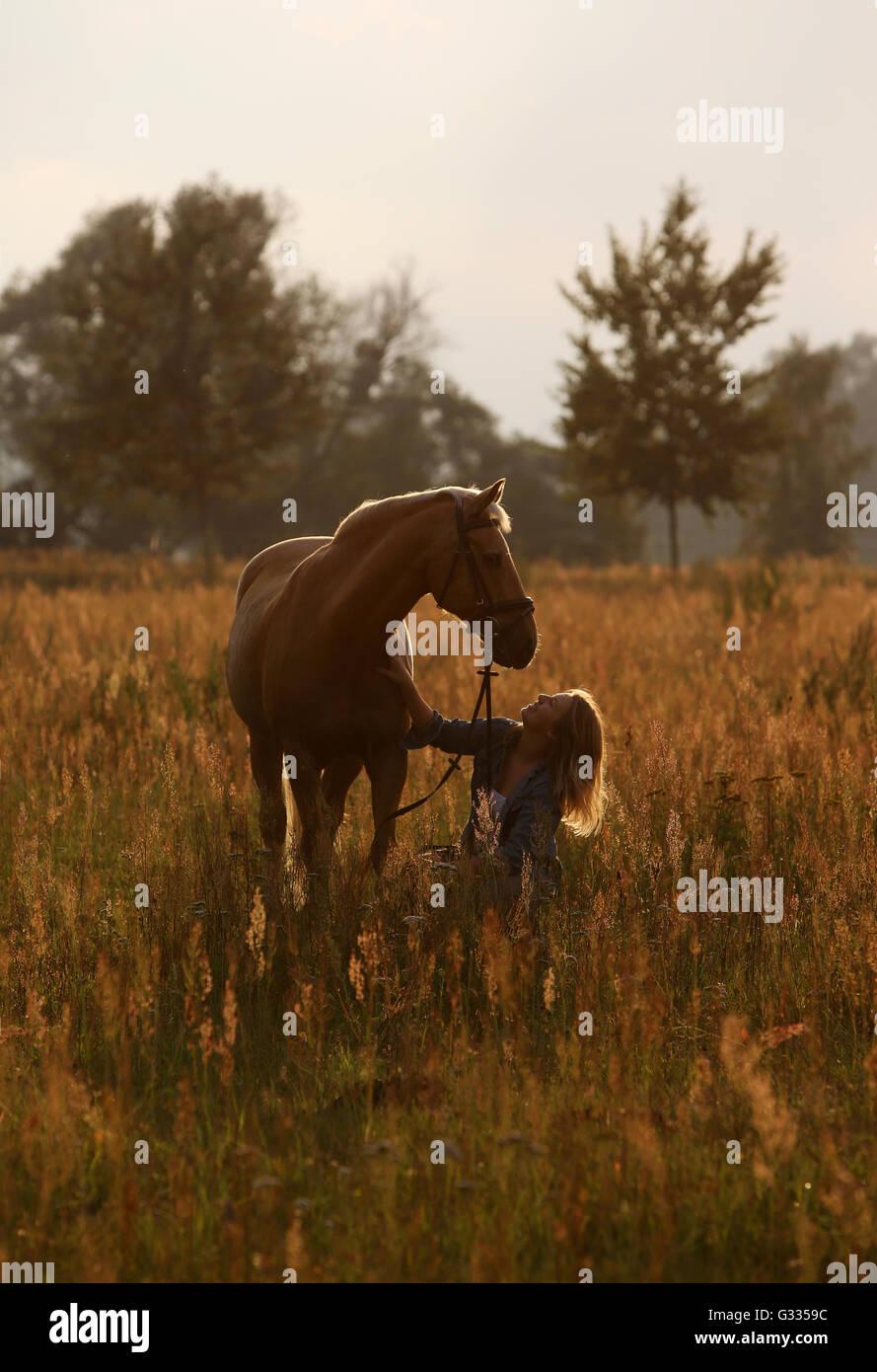 Brieselang, Allemagne, girl crouching sur une pelouse sur son cheval et regarde avec amour Photo Stock