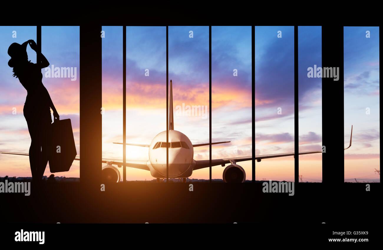 Jeune femme d'ossature à l'aéroport avec valise. Gros plan sur les passagers arrière-plan. Travel concept du transport Banque D'Images