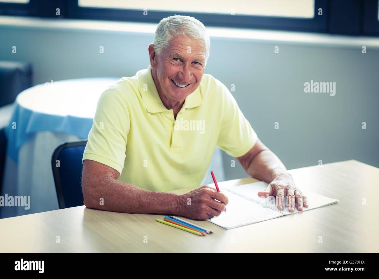 Man le dessin avec un crayon de couleur dans l'élaboration d'adresses Photo Stock