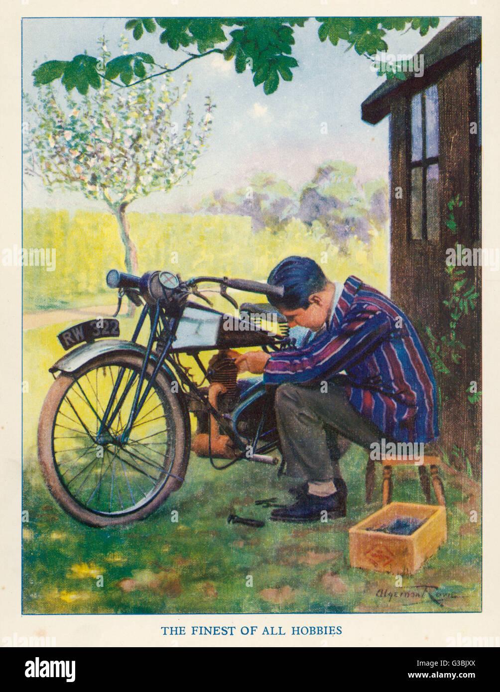 'Le plus beau de tous les passe-temps' - un garçon bricole avec sa moto. Date: 1928 Photo Stock