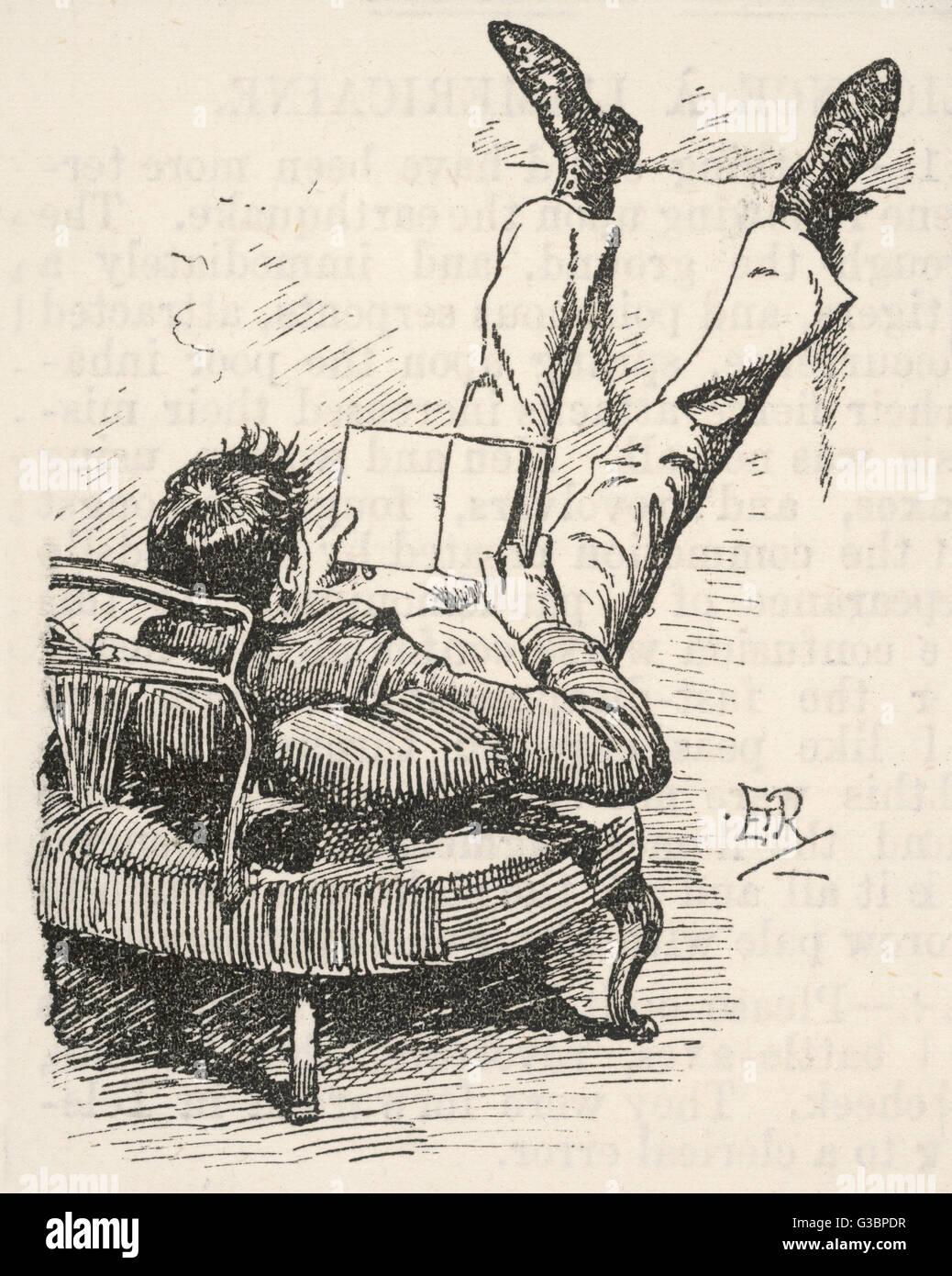 Un jeune homme, avec son haut du corps calé sur des coussins sur un lit de jour, pose ses pieds sur un rebord Photo Stock
