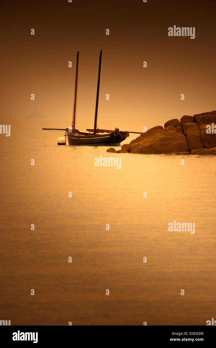 Bateau en bois amarré dans la baie du Mont Saint-Michel au coucher du soleil Photo Stock