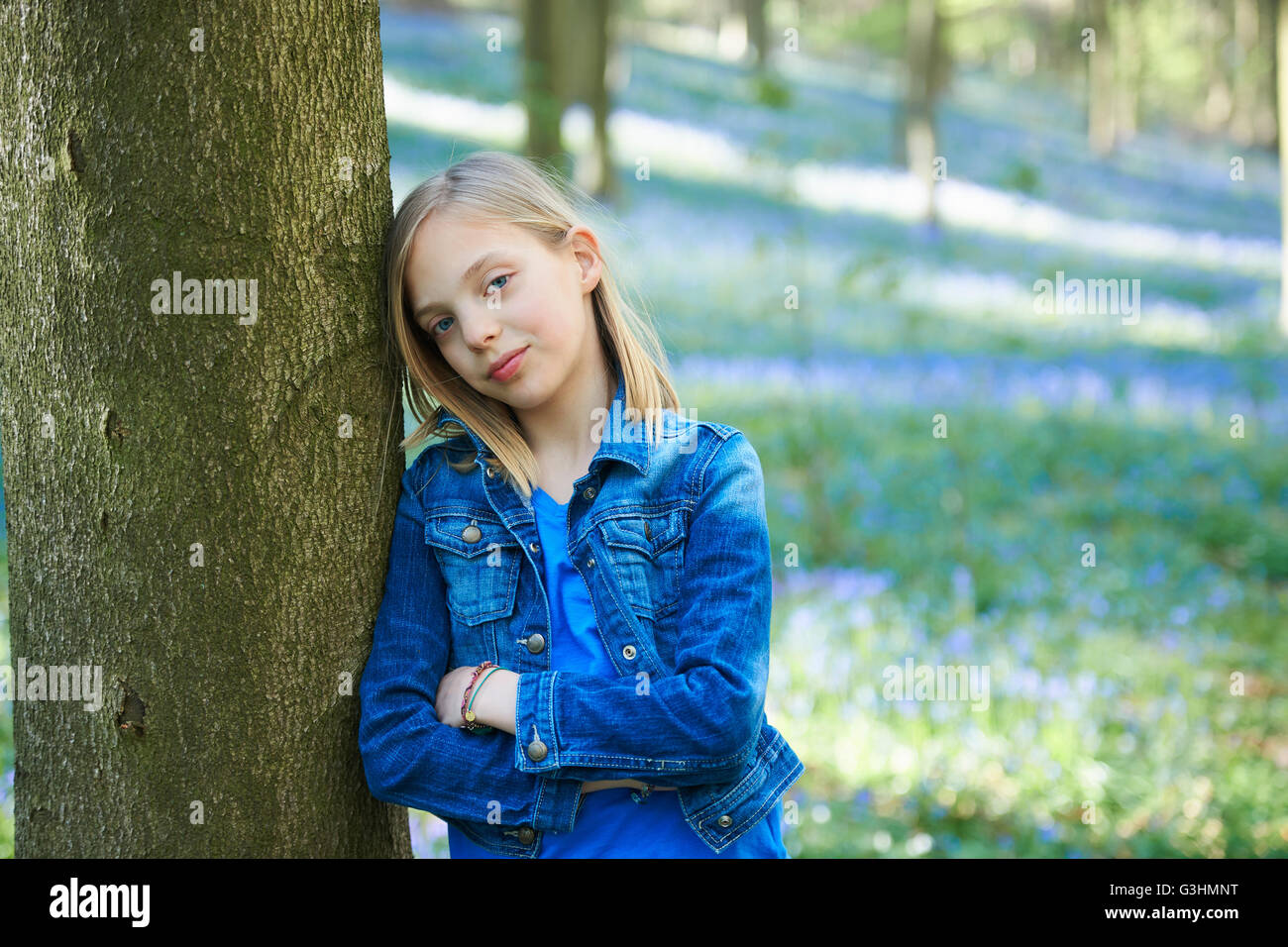 Portrait of Girl leaning against tree in forest, bluebell Hallerbos, Bruxelles, Belgique Banque D'Images