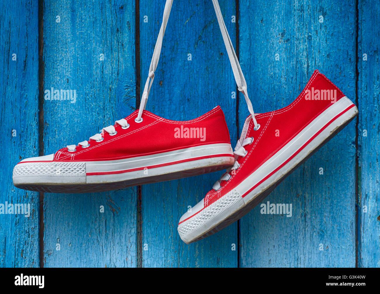 Paire chaussures en bois accrochée à un vieux rétro fond bleu Photo Stock
