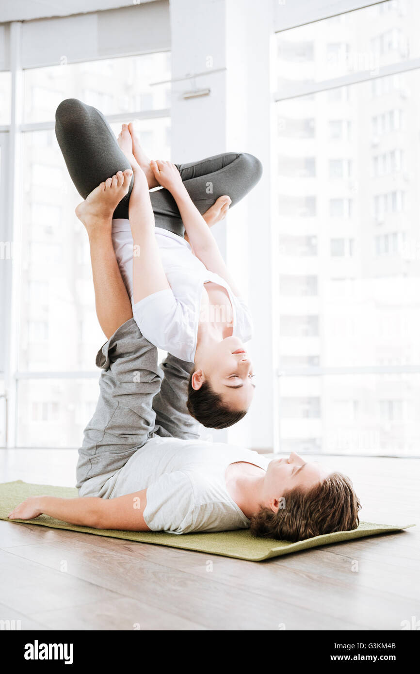 Jeune couple de faire des exercices de yoga acro en studio ensemble Photo Stock