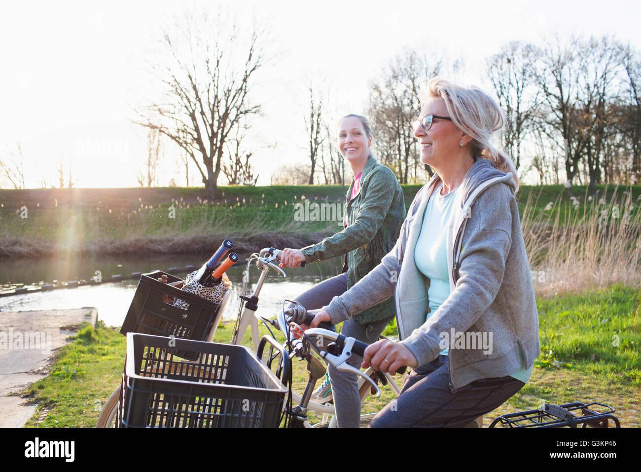 Vue latérale de la femme vélo bicyclettes par river Photo Stock