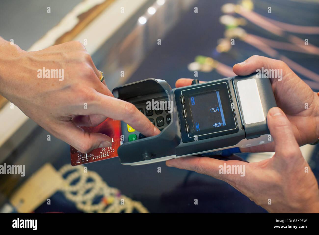 High angle view of a womans la main à l'aide de carte à puce et NIP machine Banque D'Images