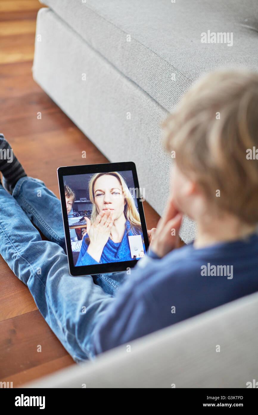 Garçon assis sur le plancher soufflant un baiser à mère sur tablette numérique appel vidéo Banque D'Images