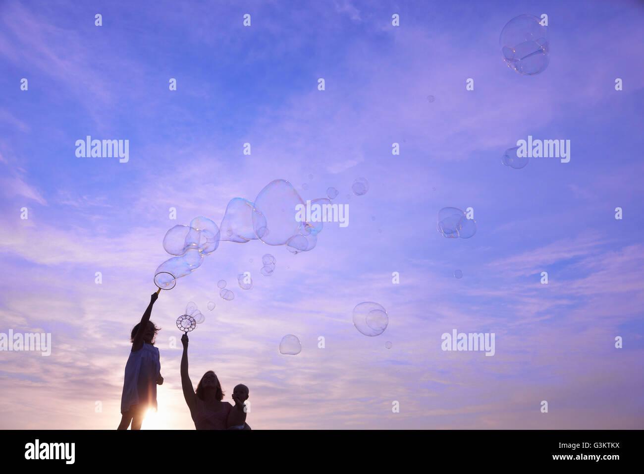 Silhouette femme avec son fils et sa fille bébé faisant des bulles sur fond de ciel bleu, Castelnuovo Berardenga, Toscane, Italie Banque D'Images