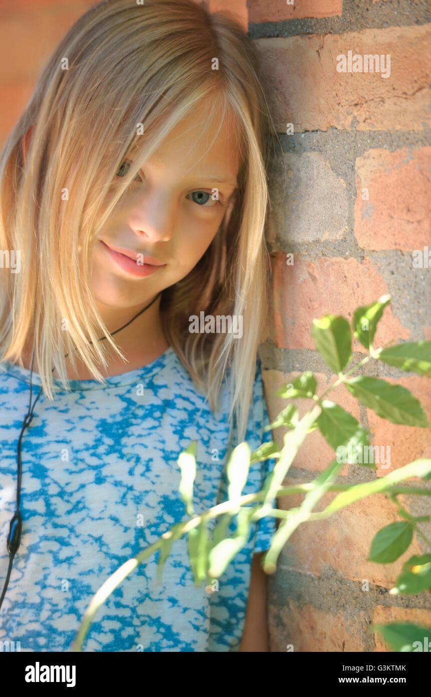 Portrait of Girl wearing earphones leaning mur de briques, Castelnuovo Berardenga, Toscane, Italie Banque D'Images