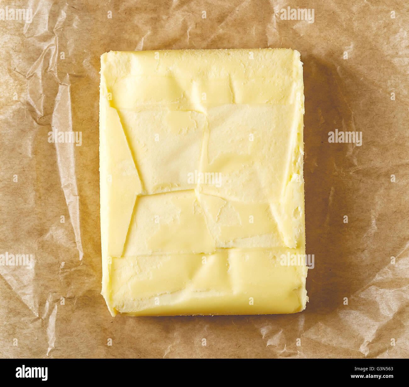 Beurre frais sur papier pergament, vue du dessus Photo Stock