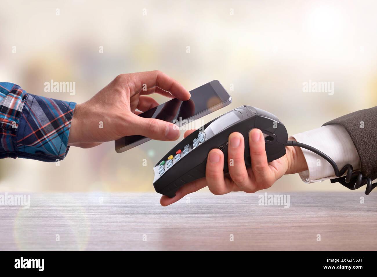 Le client paie un marchand avec téléphone mobile avec la technologie NFC. Vue d'en haut. Composition Photo Stock