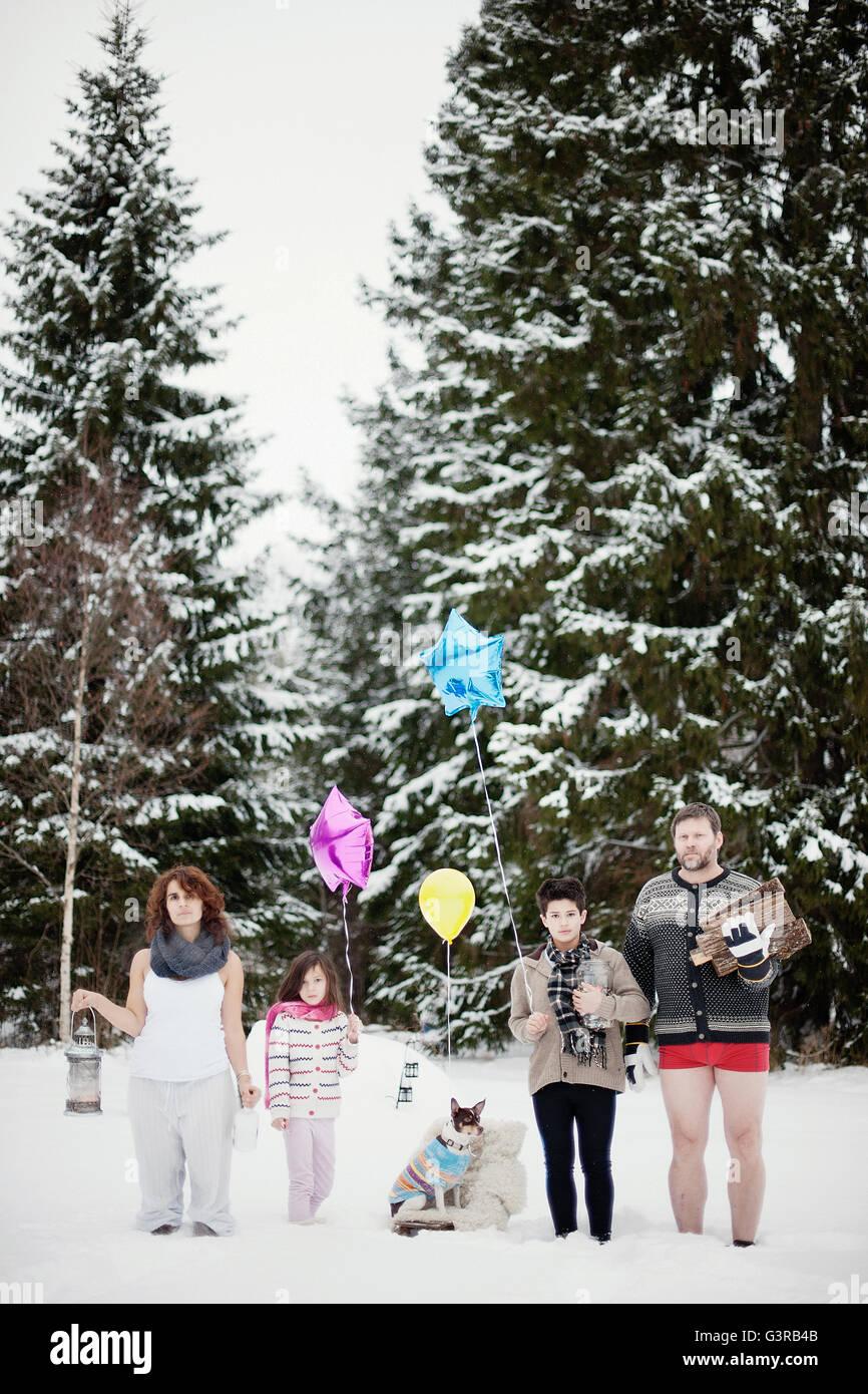 La Suède, Vastmanland, Bergslagen, famille avec deux enfants (6-7, 10,11) dans la forêt d'hiver durant Photo Stock