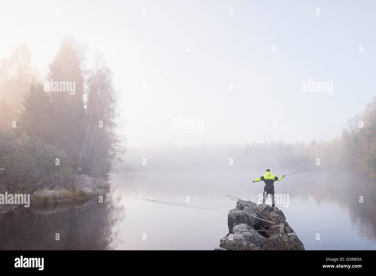 La Suède, Vastmanland, Bergslagen, Torrvarpen, jeune homme la pêche dans le lac on foggy day Photo Stock