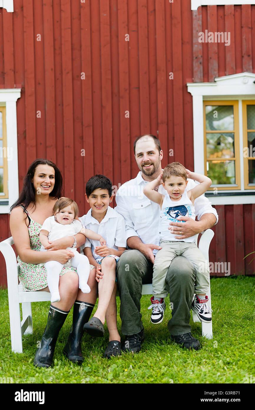La Suède, Ostergotland, Kristianstad, Gasborn, Horrsjon, Famille avec trois enfants assis sur un banc dans Photo Stock
