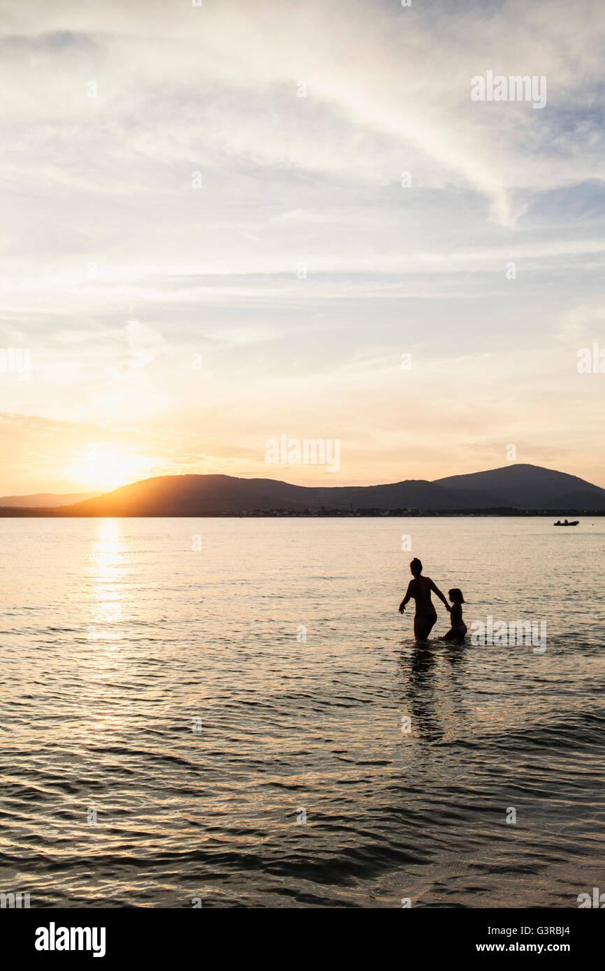 Italie, Sardaigne, Alghero, la mère et la fille de patauger dans la mer au coucher du soleil Photo Stock