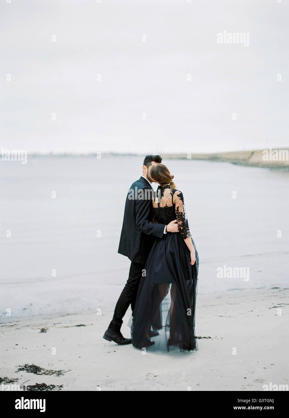 La Suède, Halland, Varberg, jeune couple walking along habillés formellement beach Photo Stock